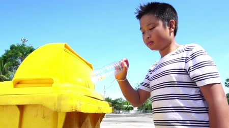 separation : Slow motion Young Asian boy drop a plastic water bottle in a yellow bin.