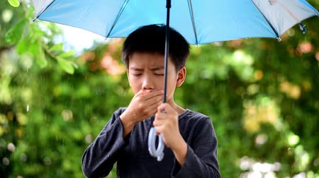 chřipka : Young Asian boy stand under the rain and feel sick.