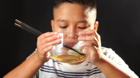 легкий : 4k Young Asian Thai boy eat instant noodle in a glass bowl on black backgound.