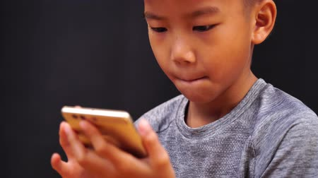 ergonomic : 4k Young Asian boy using phone to play game on internet