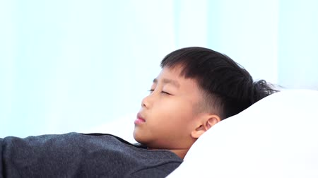 Slow motion of young Asian boy lay on a white bed 影像素材
