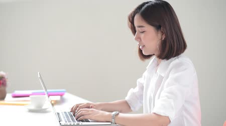 Young Asian woman working with laptop in the moden office 影像素材