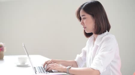 Young Asian woman working with laptop in the moden office Stockvideo