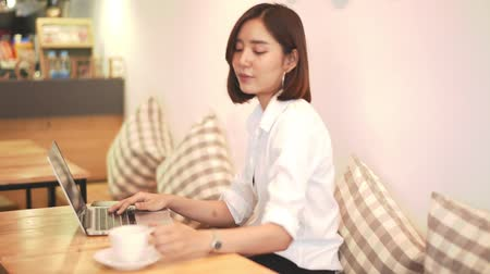Young Asian woman working with computer laptop in coffee shop 影像素材