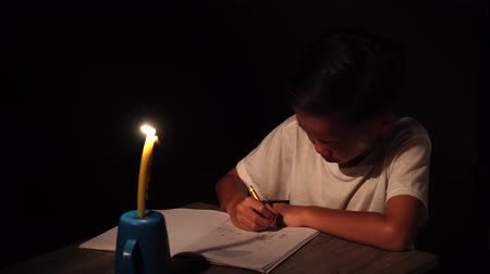 4k young Asian poor boy do homework under a candle light without electricity. Stockvideo