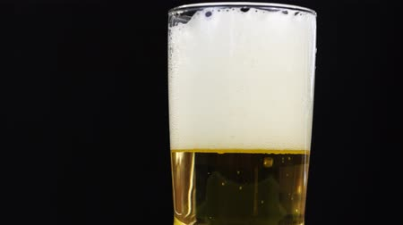 4k close up focus at beer bubble in a glass on black background