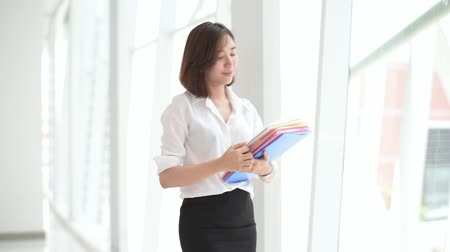 Young Asian woman carry file folder and walk in the office