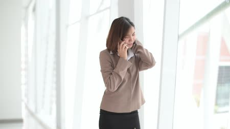 Unhappy young Asian woman walk and talk by smartphone