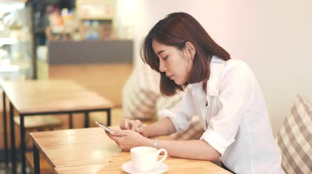 Young Asian woman play her smartphone in coffee shop 影像素材