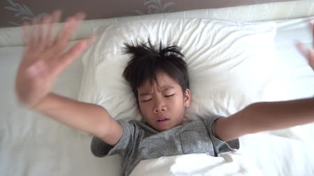 Young Asian boy wake up in the morning on white bed and feel lonely. 影像素材