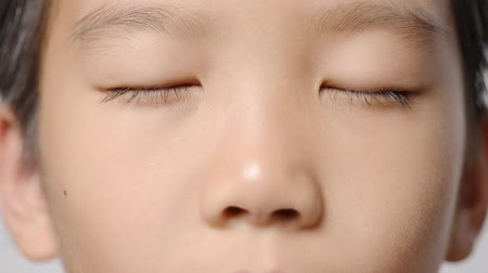 Close up at young Asian boy face and open up his eyes on white background.