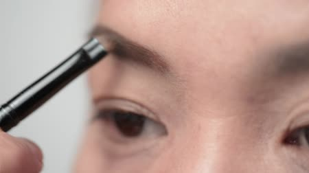 Close-up op jonge Aziatische vrouw make-up haar ooglid. Stockvideo