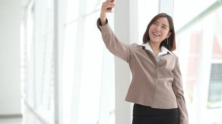 Happy Asian woman using a smartphone to do selfie at the office 影像素材