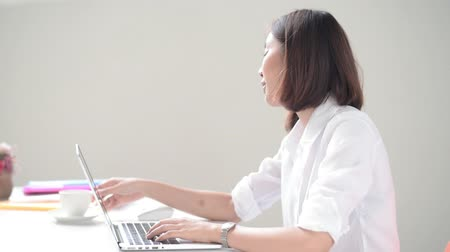 Young Asian woman working with computer and drink coffee