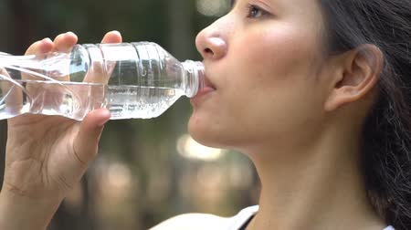 Close up slow motion camera panning and focus at young woman drink water from a plastic bottle 影像素材