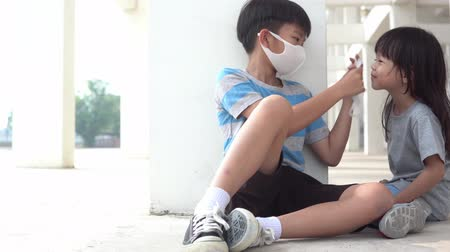 4k young Asian boy put a face mask to young girl