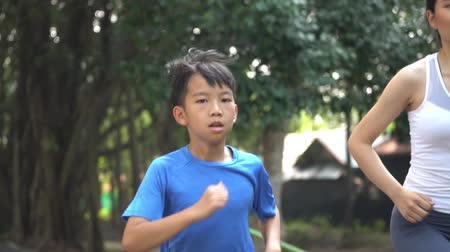 Slow motion little Asian boy running with his sister in a park 影像素材