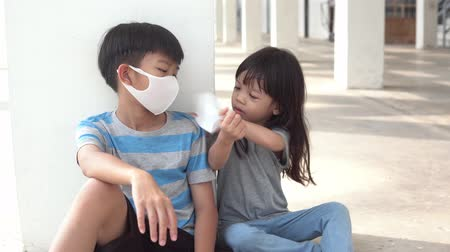 4k Move camera around young asian boy play with young girl with a face mask