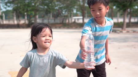 Slow motion young Asian little girl run and try to send a bottle of water Stockvideo