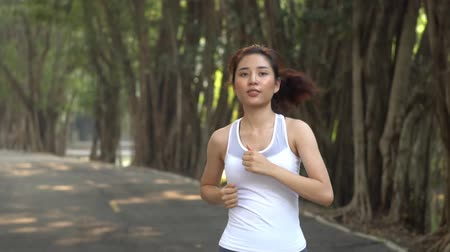 フォロー : Slow motion Follow young Asian girl running in a park during summer day