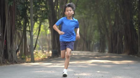 Slow motion, Young Asian boy running in a park in summer day