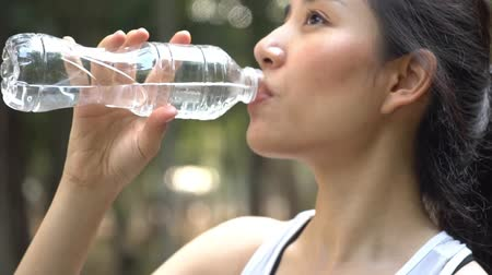 Zoom out slow motion camera panning and focus at young woman drink water from a plastic bottle