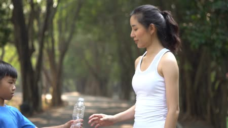 Slow motion young woman exercide in a park and get a botter of water