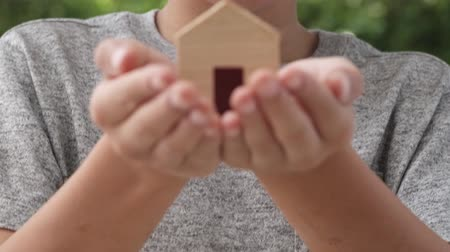 miniatűr : Slow motion at mini house model in boy hands lift to his face