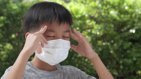 tosse : Young Asian boy wearing a face mask get headache