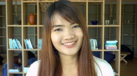könyvesbolt : Portrait of smiling beautiful asian student standing in library. Bookcase bookshelves in background. Stock mozgókép