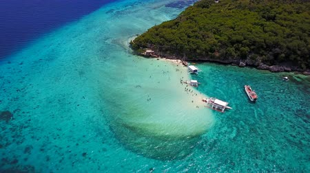 kék háttér : Aerial view flying over amazing of sandy beach with tourists swimming in beautiful clear sea water of the Sumilon island beach landing near Oslob, Cebu, Philippines.