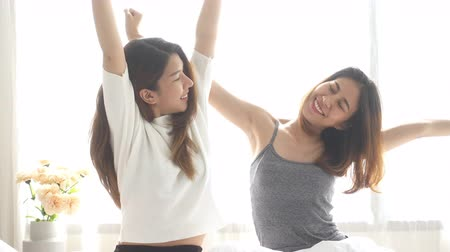 acordar : Asian women lesbian happy couple waking up in morning. Asian girls sitting on bed stretching in cozy bedroom at home. Funny women friends after wake up. LGBT Lesbian couple together indoors concept. Stock Footage