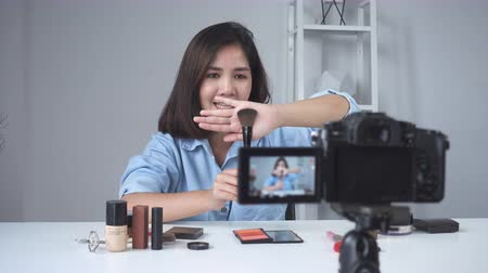 ruj : Happy smiling asian woman or beauty blogger with brush and camera recording video and waving hand at home. Beauty videoblog blogging people concept. Dolly shot.