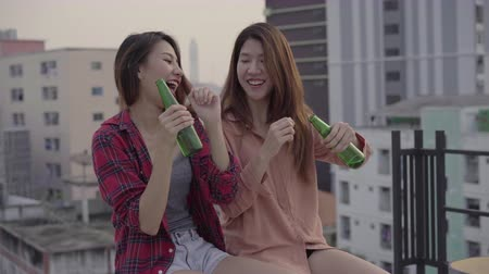 cena urbana : Group of young asian women people dancing and raising their arms up in air to the music played by dj at sunset urban party on rooftop. Young asian girls friends hanging out with drinks.