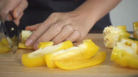 capsicum : Slow motion - Close up of woman making healthy food and chopping bell pepper on cutting board in the kitchen.