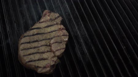 rump : Cooking chief puts uncooked meat piece on hot smoking grill with fire underneath using metal forceps, Close up slow motion. Stock Footage