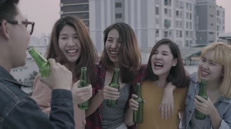 cena urbana : Slow motion - Group of young asian women and man people dancing and raising their arms up in air music played by dj at sunset urban party on rooftop. Young asian friends hanging out with drinks beer. Stock Footage