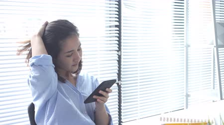 штамм : Beautiful young strain asian woman working on laptop while sitting in a living room at home. Asian business woman using phone for work in her home office. Enjoying time at home. Стоковые видеозаписи