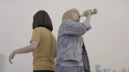 cena urbana : Slow motion - Group young asian women people dancing and raising their arms up in air to music played by dj at sunset urban party on rooftop. Young asian girls friends hanging out with drinks beer.