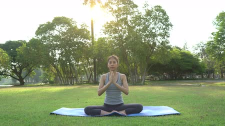 meditující : Young asian woman yoga outdoors keep calm and meditates while practicing yoga to explore the inner peace. Yoga and meditation have good benefits for health. Yoga Sport and Healthy lifestyle concept.