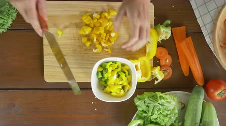 bıçaklar : Top view of woman chief making salad healthy food and chopping bell pepper on cutting board in the kitchen.
