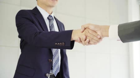 trabalho em equipe : Slow motion - Handshake to seal a deal after a job recruitment meeting. Two asian confident businessman shaking hands during a meeting in the office, success, dealing, greeting and partner concept. Vídeos