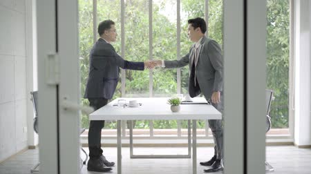 conference table : Slow motion - Handshake to seal a deal after a job recruitment meeting. Two asian confident businessman shaking hands during a meeting in the office, success, dealing, greeting and partner concept. Stock Footage