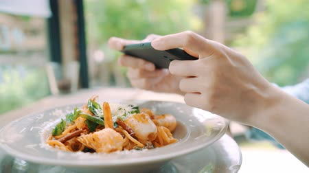 spagetti : Female blogger photographing lunch in restaurant with her phone. A young woman taking photo of spaghetti food on smartphone, photographing meal with mobile camera.