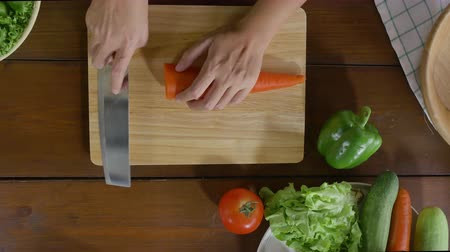 placa de corte : Top view of woman chief making salad healthy food and chopping carrot on cutting board in the kitchen.