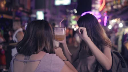 друзья : Slow motion - Traveler backpacker Asian women lesbian lgbt couple dancing together. Female drinking alcohol or beer with friends and having party at The Khao San Road in Bangkok, Thailand.