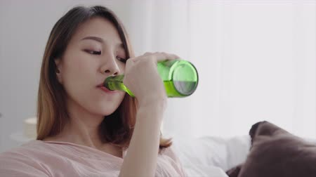 enforcamento : Happy asian woman drinking beer and watching TV sitting on a couch in the living room at home.