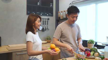 relação : Asian man prepare salad food in the kitchen. Beautiful happy asian couple are cooking in the kitchen. Young asian couple have romantic time while staying at home. Couple lifestyle at home concept. Stock Footage