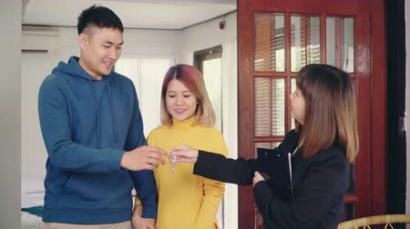 real : Happy young Asian couple and agent. Cheerful young man signing some documents while sitting at desk together with his wife. Buying new house real estate. Signing good condition contract.