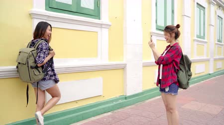 lesbian couple : Traveler backpacker Asian women lesbian lgbt couple travel in Bangkok, Thailand. Tourist blogger young female couple using smartphone takes photos. Stock Footage